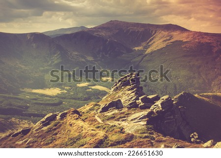 Autumn mountain and hills landscape and stone boulders in the foreground. Filtered image:cross processed vintage effect.  - stock photo