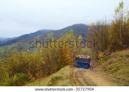 autumn mountain dirty road and old log truck