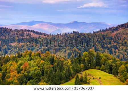 Autumn mountain landscape with colorful trees in forest. Sky with clouds over hazy hills