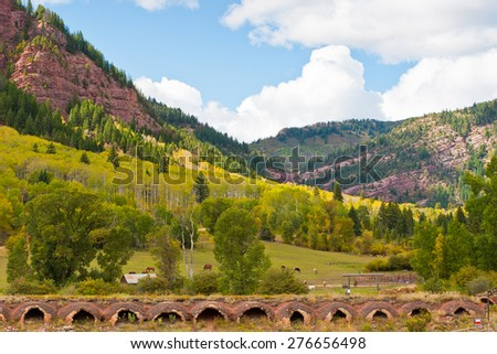 Autumn mountain  landscape with old coal ovens on foreground in Colorado, USA. - stock photo
