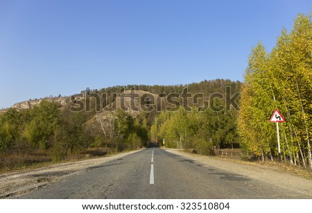 autumn mountains, the winding road sign. - stock photo