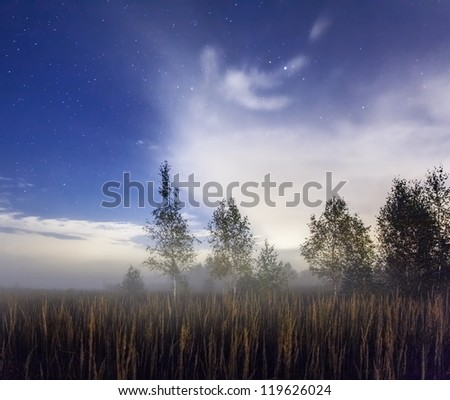 autumn night field alight with bright stars and clouds - stock photo