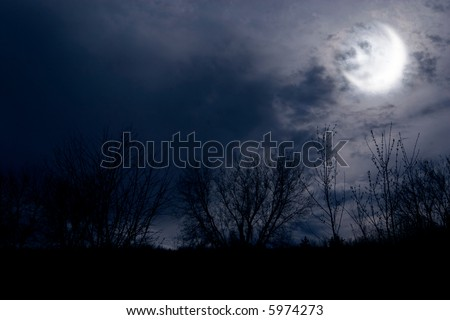 autumn night forest alight with bright moon in clouds - stock photo