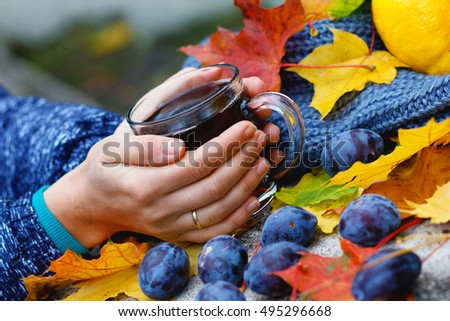 Autumn. October. Girl on the nature of drinking tea.  Against the background of lemon, scarf, plum and fallen leaves