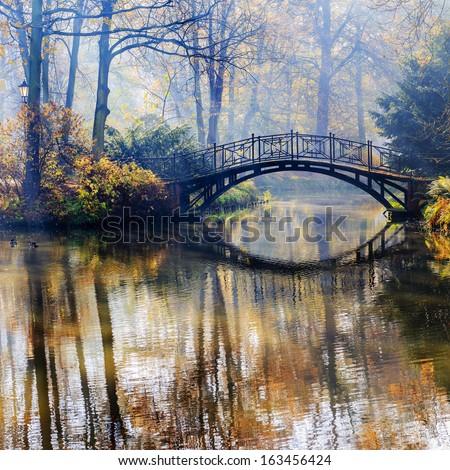 Autumn - Old bridge in autumn misty park - stock photo