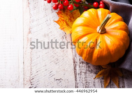 Autumn old wood background with pumpkin, pine cone, berries, yellow leaves and rowan. Selective focus. With copy space. - stock photo