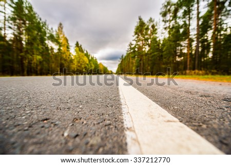 Autumn on the country road, yellowed foliage of trees near the roadside. View from the level of the dividing line - stock photo
