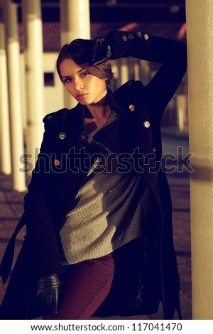 autumn or spring stylish dressed young attractive woman standing in beautiful location or exterior