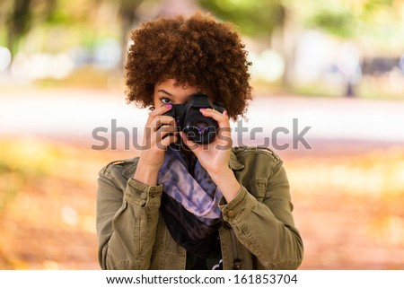 Autumn outdoor portrait of beautiful African American young woman holding a digital camera - Black people - stock photo