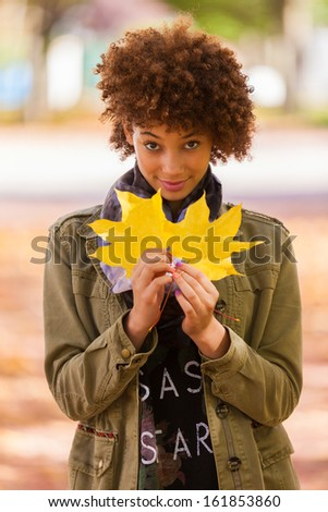 Autumn outdoor portrait of beautiful African American young woman holding yellow leaves - Black people - stock photo