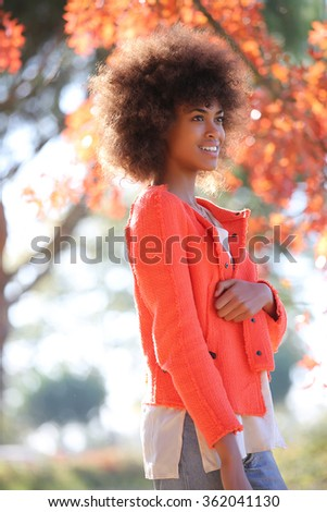 Autumn outdoor portrait of beautiful African American young woman in park. - stock photo