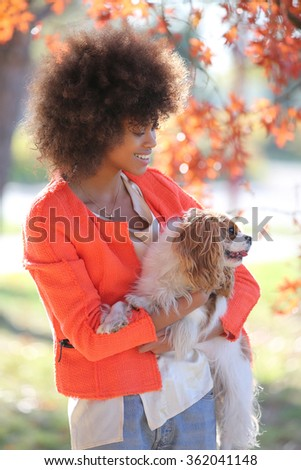 Autumn outdoor portrait of beautiful African American young woman in park playing with her dog - stock photo