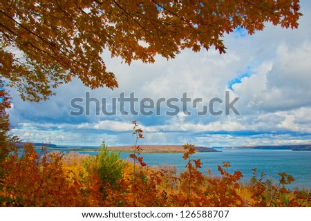 Autumn overlook with colorful foliage overhang and blue water in distance