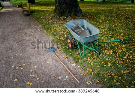 Autumn Park. Wheelbarrow for cleaning leaves standing near the road.