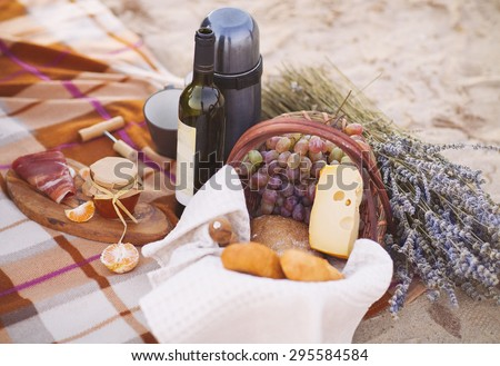 Autumn picnic by the sea with wine, grapes, bread,  jam and cheese - stock photo