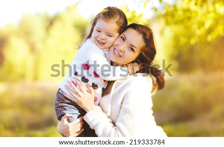 Autumn portrait happy smiling mother and child outdoors - stock photo