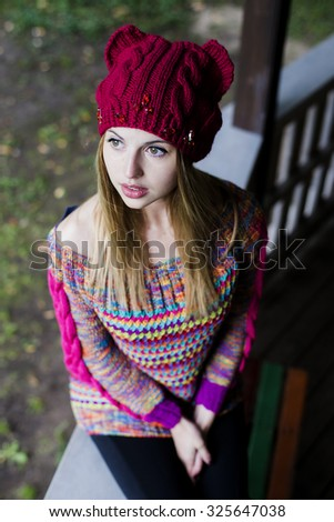 Autumn portrait in nature, a very beautiful woman in a knitted cap with ears