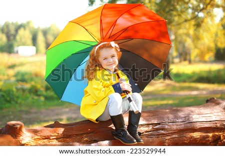 Autumn portrait little girl with colorful umbrella outdoors in park - stock photo