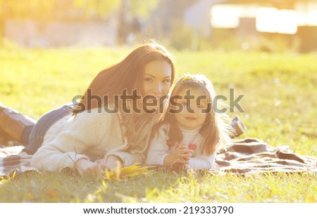 Autumn portrait mother and child smiling on the grass  - stock photo