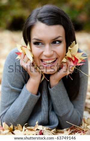 Autumn portrait of a beautiful playful girl, lying on the ground in a park. Selective focus. - stock photo
