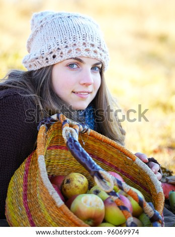 Autumn portrait of a beautiful 20 year old woman outdoor with fruit basket. - stock photo