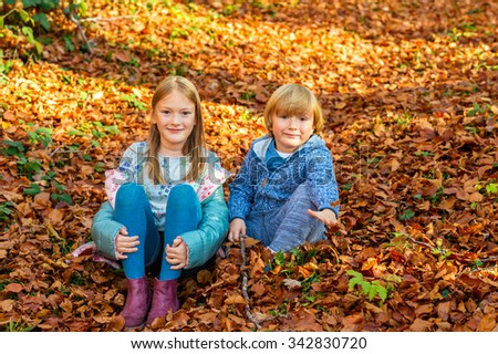 Autumn portrait of a cute girl and her little brother, playing in forest  - stock photo