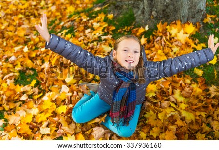 Autumn portrait of a cute little girl of 8 years old, playing with yellow leaves in the park - stock photo