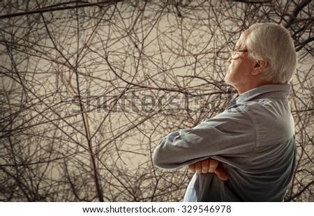 Autumn. Portrait of a senior man thinking about something - stock photo