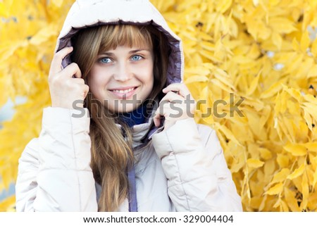Autumn portrait of a woman in a hooded jacket - stock photo