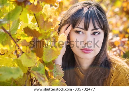 Autumn portrait of a young woman on a background of leaves