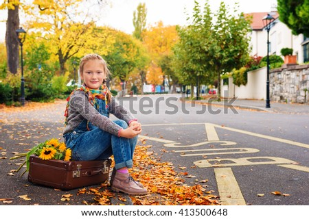 Autumn portrait of adorable little blond girl of 8 years old, wearing warm pullover, denim overalls and beige shoes, sitting on the old vintage suitcase - stock photo