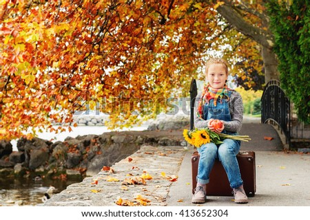 Autumn portrait of adorable little blond girl of 8 years old, wearing warm pullover, denim overalls and beige shoes, sitting on the old vintage suitcase, holding red apple and yellow sunflowers - stock photo