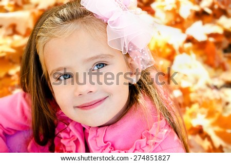 Autumn portrait of adorable little girl with maple leaves outdoor