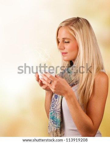 Autumn portrait of beautiful blond woman drinking tea - stock photo