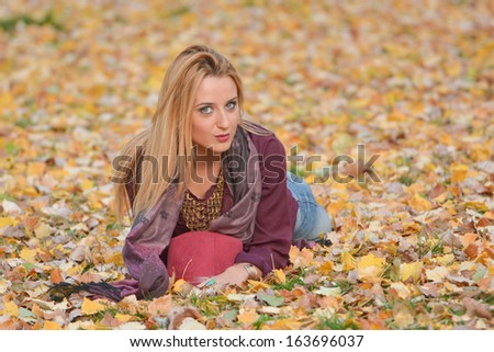 Autumn portrait of beautiful girl laying on leaves