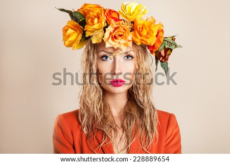 Autumn portrait of blonde beautiful woman with flowers on head. Girl looking at camera.