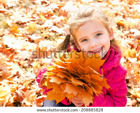 Autumn portrait of cute smiling little girl with maple leaves outdoor - stock photo