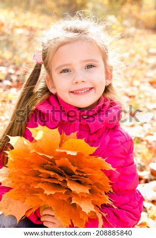 Autumn portrait of cute smiling little girl with maple leaves outdoor