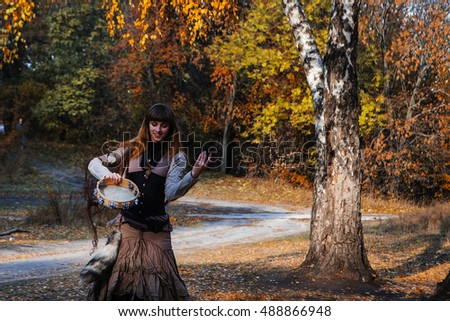 autumn portrait of dancing woman with a tambourine