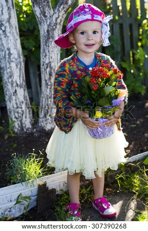 Autumn portrait of the little girl outdoors with flowers