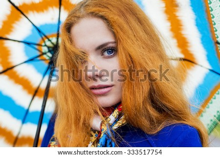Autumn portrait of the woman with fiery hair in leaves with umbrella - stock photo