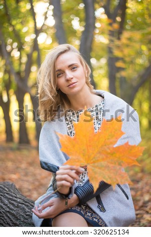 Autumn portrait of young adult woman in fall colors outdoors holding in hand leaf of yellow maple leaves against fall park background Empty copy space for inscription