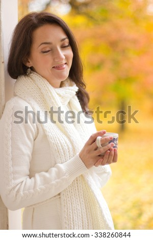 Autumn portrait of young brunette woman in white sweater with a cup of coffee or tea