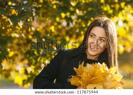 Autumn portrait of young woman in fall colors outdoors holding a bunch of yellow maple leaves looking to the side - stock photo