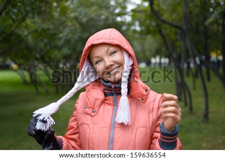 Autumn portrait of young woman in red jacket in the park