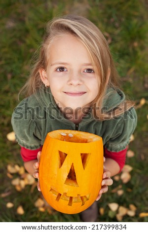 Autumn portrait with a Halloween pumpkin jack-o-lantern - little girl looking up - stock photo