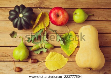 Autumn pumpkin and fruits on wooden table - stock photo