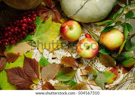 Autumn pumpkin composition on wooden table with autumn leaves and apples