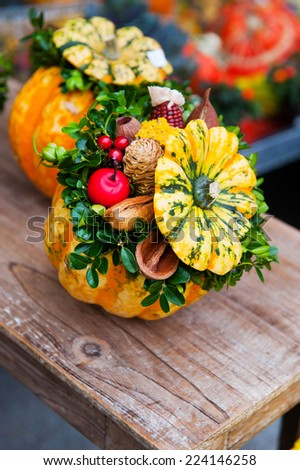Autumn pumpkin with leaves and flowers on wooden board - stock photo