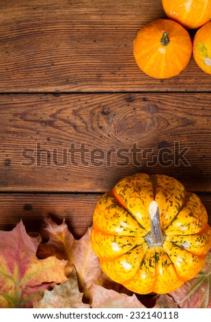 Autumn pumpkins on wooden table with leaves - stock photo
